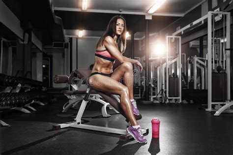 bench body women fitness girl with shaker posing on bench in the gym stock