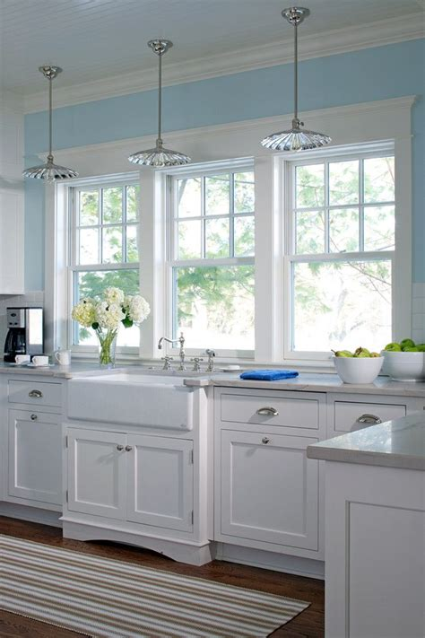 white kitchen cabinets blue walls glass pendant lighting white farm sink kitchen windows
