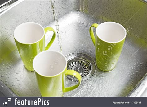 washing cup image of washing green cups in the kitchen sink