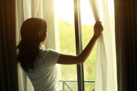 woman opening curtains why bedroom curtains are important to your sleep the