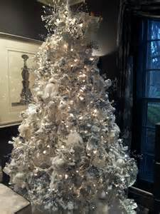 fresh flocked christmas tree decorated in white sliv