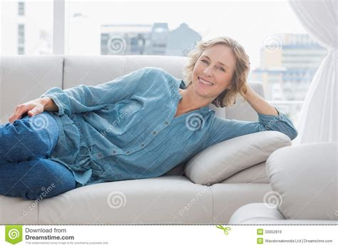 relaxing on the couch smiling woman relaxing on her couch royalty free stock