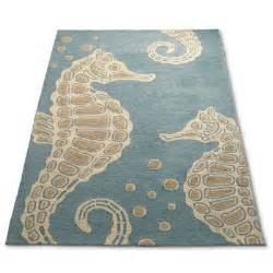 soft teal outdoor rug with beige seahorse motif