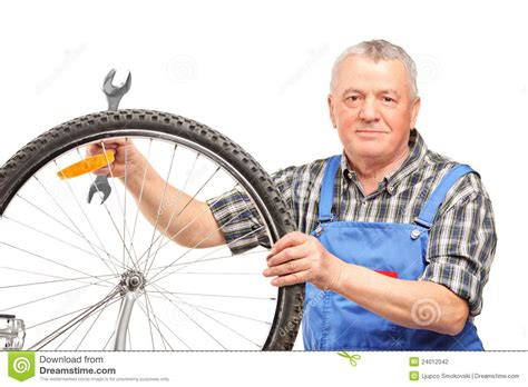 man holding man holding wrench and repairing bicycle wheel stock