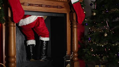 santa father christmas coming down the chimney stock