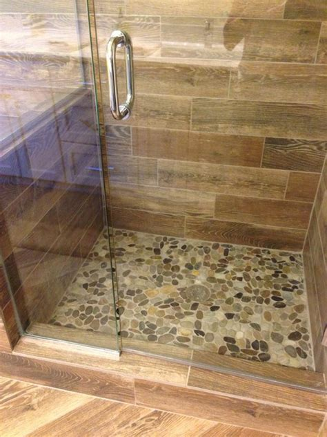 wood look tile bathroom shower remodel look with mosaic flat rock pebbles