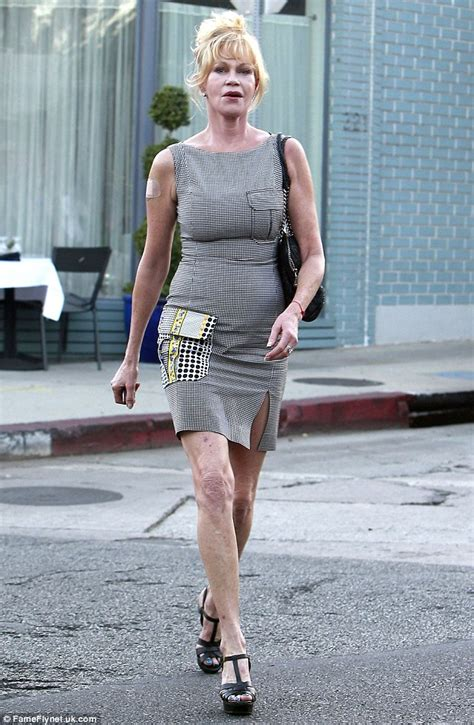 melanie griffith puffs on a cigarillo over lunch in