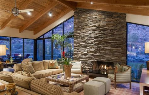 Living room with glass walls and huge stone fireplace home design