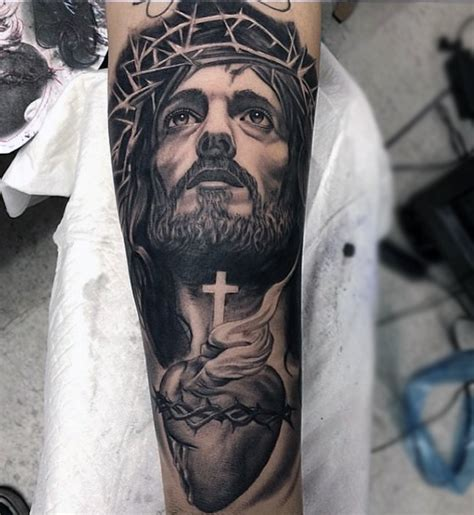tattoo in jesus man with tattoo of jesus holding cross and heart forearm