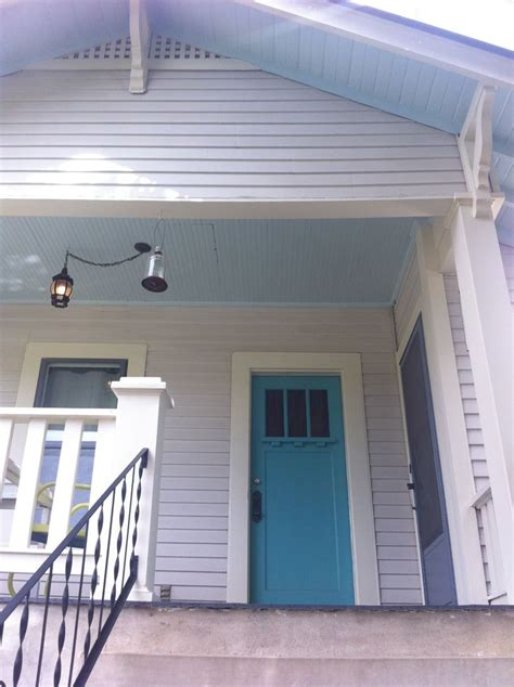 light gray almost white house turquoise door with pale
