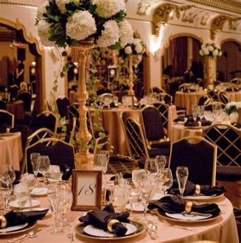 themed black tie events tall centrepieces with white flowers and gold details