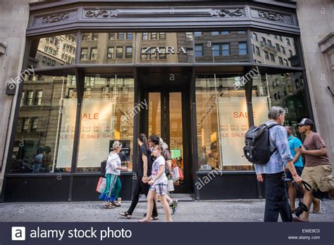 shoppers pass a zara clothing store on fifth avenue in new