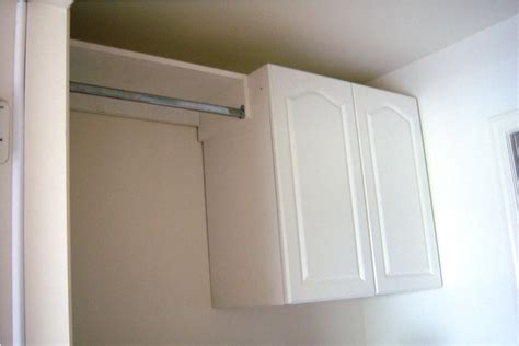 Attractive Small Cabinet Kitchen #8: Simple-Laundry-Room-Cabinets-in-White-Color-beside-Clothes-Hanger-inside-Small-Room.jpg