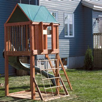 play structure backyard an elevated play fort has a slide rope ladder and a