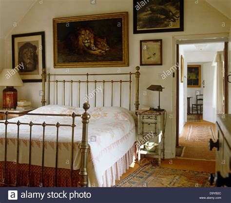brass bedroom paintings of lions on wall above brass bed with white and