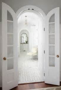 Arched bi fold doors open to a master bathroom featuring a paneled