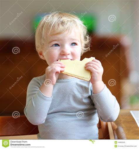 Funny little girl eating sandwich at home
