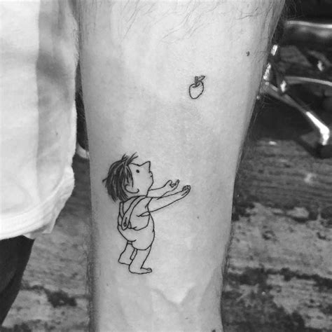 small boy tattoos illustration of the giving tree on the forearm
