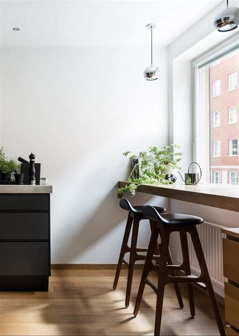 An elegant black kitchen with a cafe style eating space