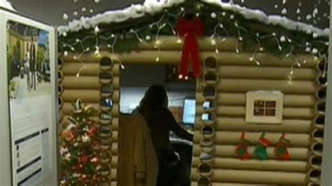 woman transforms cubicle into holiday themed log cabin