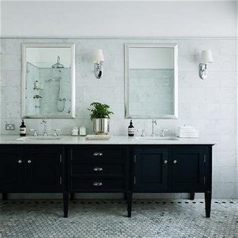 Elegant bathroom features a footed black dual washstand topped with