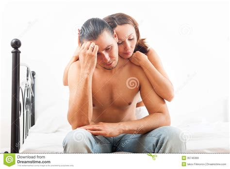 man and woman sexuality in bedroom man has sad face woman consoling him on bed in bedroom