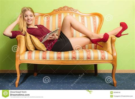 laying on my couch fashion woman laying on sofa with pc tablet stock photo