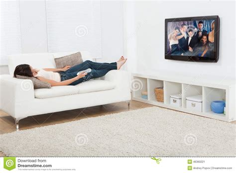 sofa tv woman watching television while lying on sofa stock photo