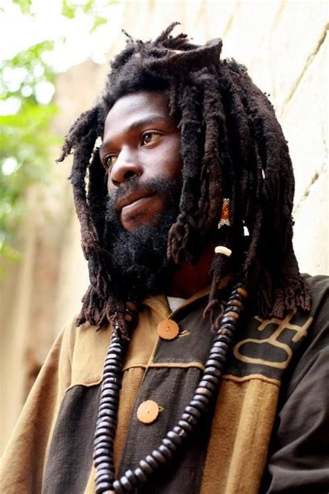 rastafarian hair a young man with a full beard and thick dreadlocks gazes