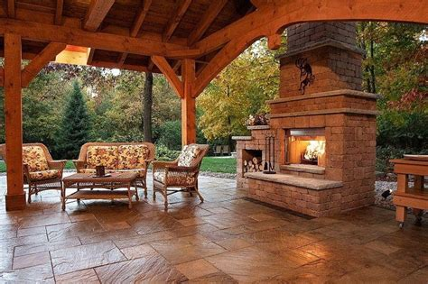 wood and stone backyard covered patio and fireplace reminds me of texas hill country type living