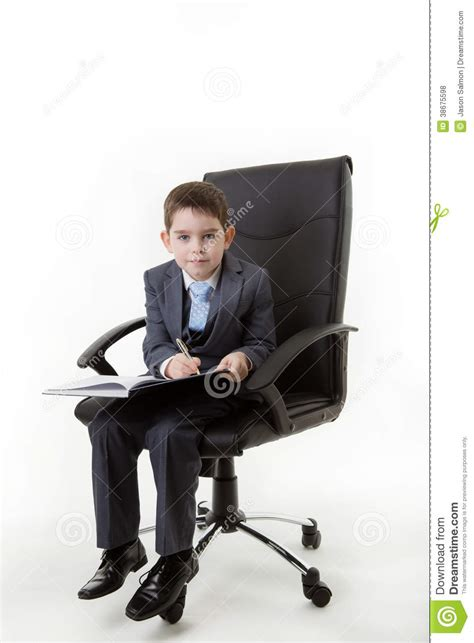 Person Sitting In Chair by Kid Dressed Up As A Business Person Royalty Free Stock