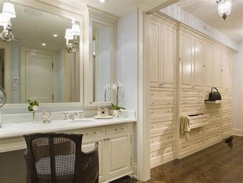 in closet with white built shelves and cabinets vanity