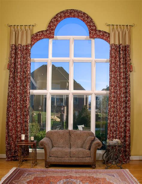 Custom window treatment for large arched window and brown couch plus mismatched side tables