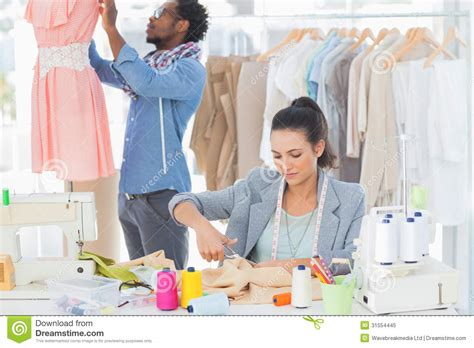 dress design and cutting fashion designer cutting textile at desk royalty free
