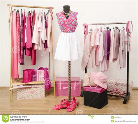 Wardrobe Of Clothes Dressing Closet With Pink Clothes Arranged On Hangers And