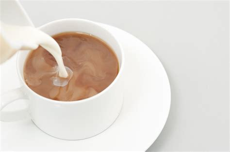 Milk Capuccino pouring milk into a cup of coffee free stock image