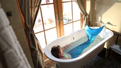 bathtub costume 9 year old girl with fake mermaid costume in bathtub stock