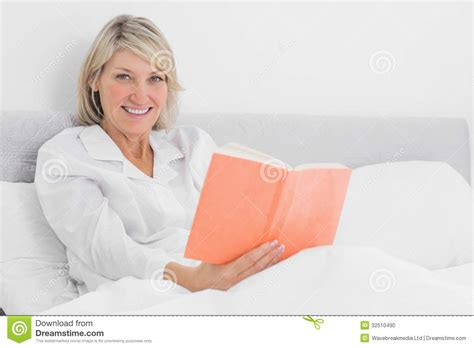 sitting in bed blonde woman sitting in bed reading smiling at camera