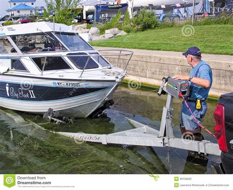 winching a boat on a trailer man at boat launch loading a fishing boat on trailer