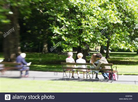 sitting park bench people sitting on park benches in a city a young couple