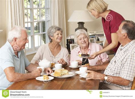 help with housing group of senior couples enjoying afternoon tea together at