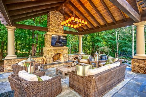 outdoor living room with fireplace patio with outdoor kitchen tub and koi pond