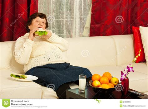 woman eats couch elderly eating sandwich home royalty free stock image