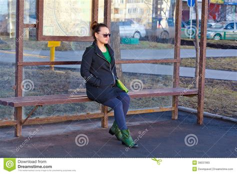 sitting on the bench waiting for you girl waiting for transport at the bus stop stock photo