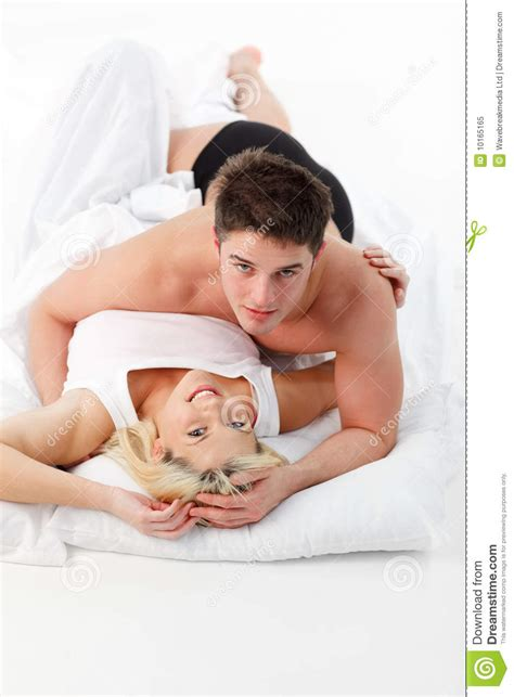 love in bed couple in love in bed looking at the camera royalty free