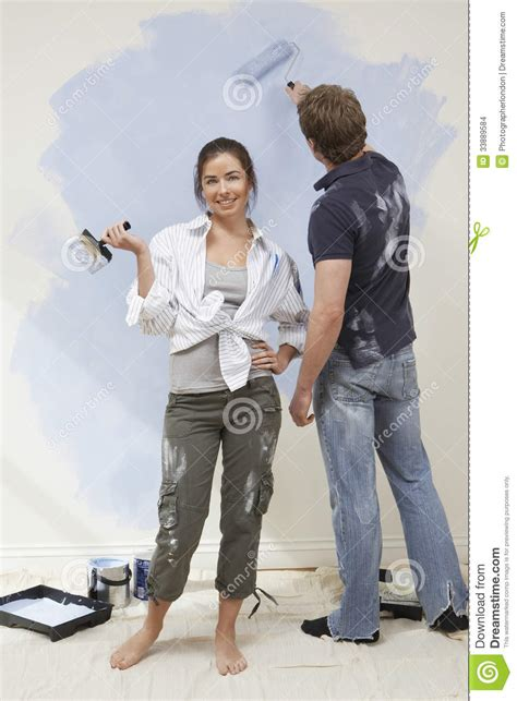 looking for a man who paints houses woman holding paintbrush while man painting wall stock
