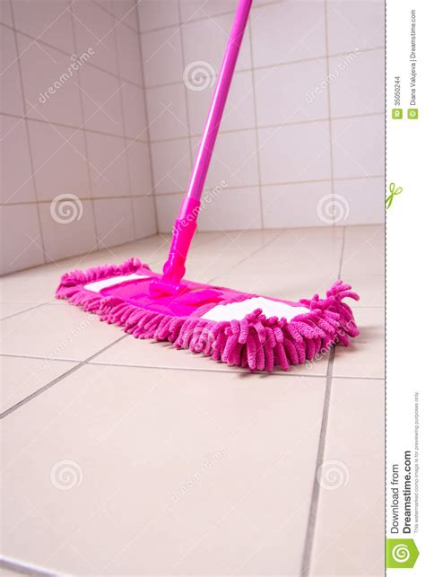 mopping bathroom floor pink mop cleaning tile floor in bathroom stock photo