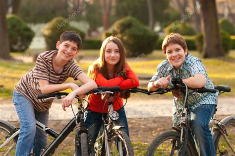 soap two girls and one boy two smiling boys and one on bicycles in the park stock photo