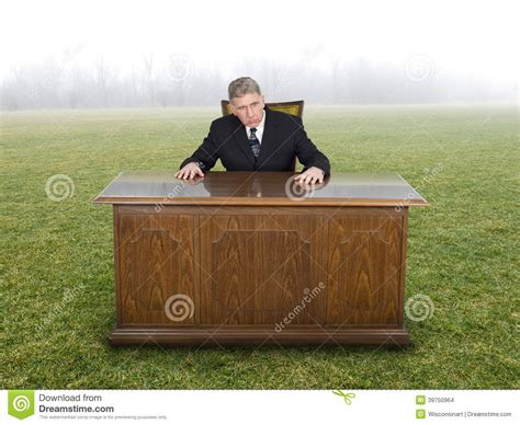 Desk In The Field by Businessman Sits At Office Desk In Field Or Meadow Stock