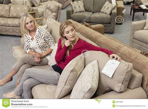 looking for sofas mother and daughter sitting on sofa while looking at price